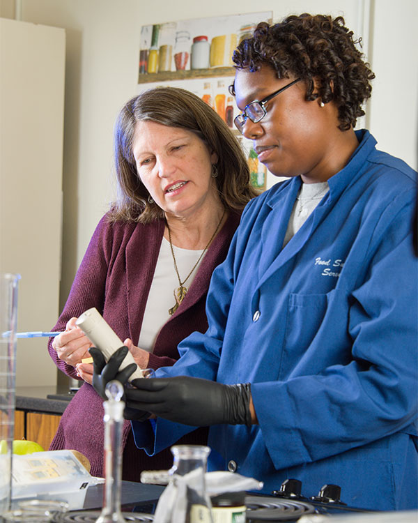 Dr. Marisa Bunning helping student in lab